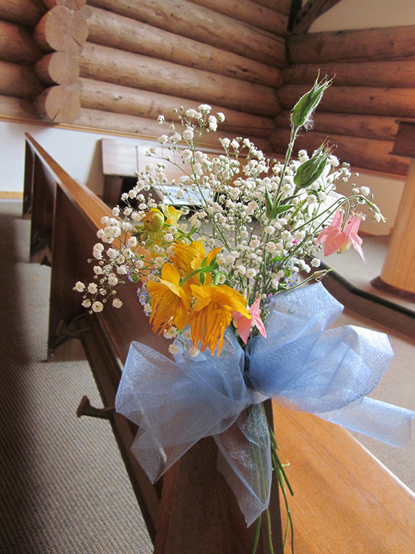 Flowers Hung on end of Pew